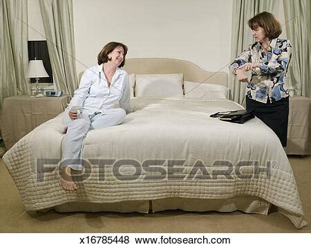 Two mature women in bedroom, one getting dressed, other in
